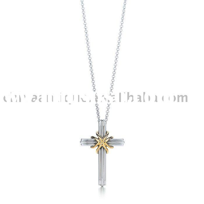 "Cross pendant. Sterling silver, with eighteen karat gold, on an 18"" chain."